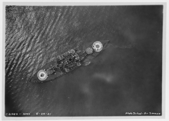 An Army Air Service plane photographs Coast Battleship No. 4 from above during the bombing tests off the Virginia capes, 25 June 1921. Note the large targets painted fore and aft. (Naval History & Heritage Command Photograph NH 93549)