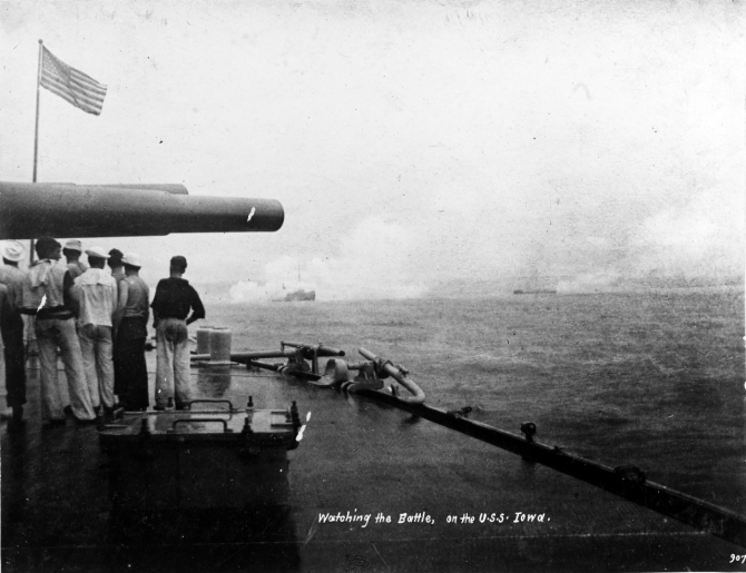Sailors watch the Battle of Santiago de Cuba from Iowa's deck, 3 July 1898. Note the dense smoke around the ship in the left center, and the close range of the Spanish ships, ablaze from the American gunfire. (Naval History & Heritage Command Photograph NH 1132, copied from the Journal of Naval Cadet Cyrus R. Miller)