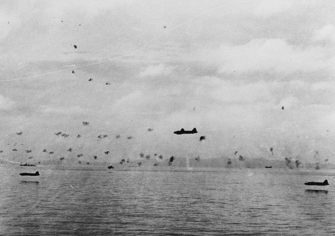 Japanese Mitsubishi G4M1 Type 1 attack planes fly low through Allied antiaircraft fire to attack the transports maneuvering between Guadalcanal and Tulagi, 8 August 1942. The planes carry torpedoes and have had their bomb-bay doors removed, and a bomber similar to the ones in this picture torpedoed Jarvis during the desperate battle. (U.S. Navy Photograph 80-G-17066, National Archives and Records Administration, Still Pictures Branch, College Park, Md.)
