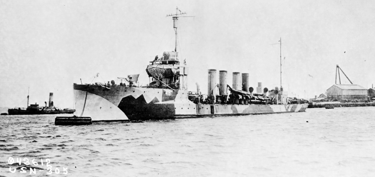 "Jenkins moored in a European port (likely Queenstown), circa 1918, in ""dazzle"" camouflage. Note the splinter mattresses protecting her bridge and the shield on her forward 3-inch gun. (Naval History and Heritage Command Photograph NH 52009)"