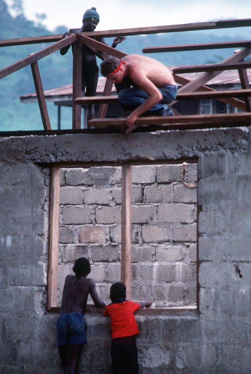 A Jesse L. Brown crewman helps put a new roof on a school at Freetown, Sierra Leone, as some of the students give him a hand during West African Training Cruise 84. Photo from the April 1984 issue of All Hands Magazine. (U.S. Navy Photograph DN-ST-85-08489, PH2 Jeffrey A. Salter, National Archives and Records Administration, Still Pictures Division, College Park, Md.)
