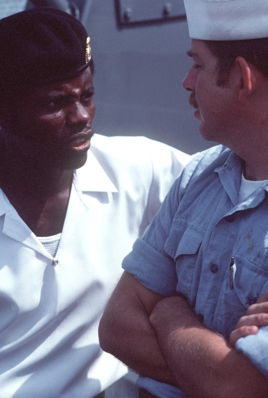 A crewman from Jesse L. Brown speaks with a West African sailor who is touring the ship during West African Training Cruise 84. Photo from the April 1984 issue of All Hands Magazine. (U.S. Navy Photograph DN-ST-85-08490, PH3 Roger Frazer, National Archives and Records Administration, Still Pictures Division, College Park, Md.)