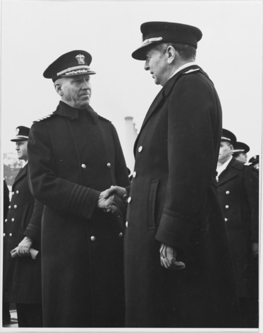 Rear Adm. Adolphus Andrews, Commandant, Third Naval District, congratulates Capt. Lyman K. Swenson (left), the ship's commanding officer, at Juneau's commissioning.  (Naval History and Heritage Command Photograph NH 52360)