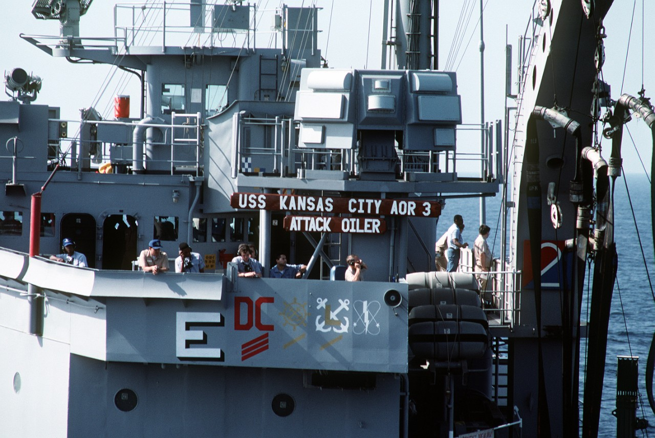 Officers and crewmen stand on Kansas City's bridge wing during an underway replenishment, April 1991. Note the award symbols painted on the hull, including the large white E signifying the Battle E Award, which Kansas City won for the year 1990. (U.S. Navy Photograph DN-ST-91-09120, JO1(SW) Gregg Snaza, National Archives and Records Administration, Still Pictures Division, College Park, Md.)