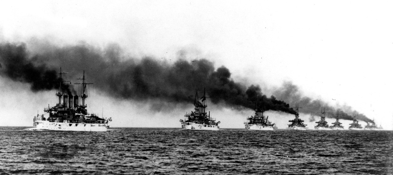 The Great White Fleet steams in column from Hampton Roads, Va. at the beginning of their cruise around the world, 16 December 1907. Kansas (Battleship No. 21) (left) and Vermont (Battleship No. 20) (next in line) lead the ships in this C.E. Waterman image. (Naval History and Heritage Command Photograph NH 92091)