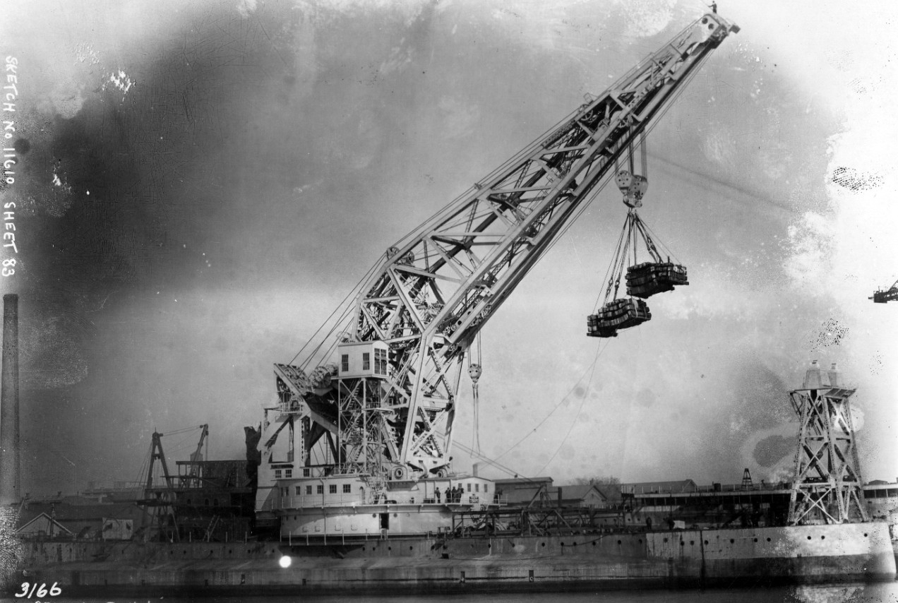"Testing continues on Crane Ship No. 1's 250-ton revolving crane while she undergoes conversion at Philadelphia Navy Yard, 30 October 1922. The ship lifts a 312-ton load on the right and left main hoist with equalizer at 101-foot reach on an even keel. Jib fore and aft at an angle of 38°46"". (Naval History and Heritage Command Photograph NH 60251)"