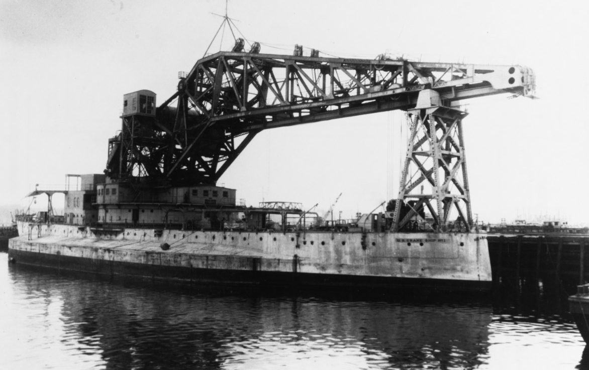A view of Crane Ship No. 1 at Puget Sound Navy Yard as she prepares to shift to the east coast, spring 1936. Note that her stern bears the names Kearsarge and Crane Ship No. 1, a fact that will contribute to Secretary of the Navy Frank Knox later authorizing the service to drop the name Kearsarge and for the vessel to be known only as Crane Ship No. 1. (Naval History and Heritage Command Photograph NH 43456)