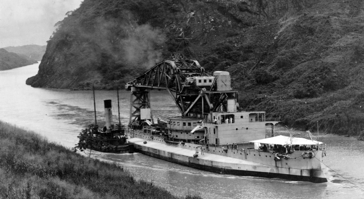 Crane Ship No. 1 passes through the Gaillard Cut of the Panama Canal, most likely during her shift between the coasts, 15 June–21 August 1926. Note the awning spread forward to protect her men from the scorching tropical sun. (Naval History and Heritage Command Photograph NH 52037)