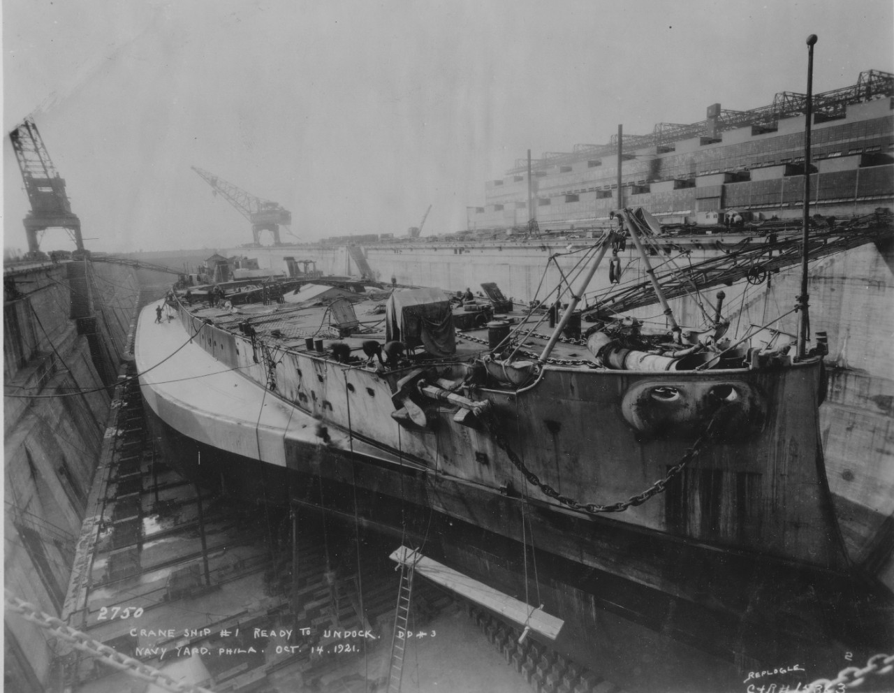 Stripped of turrets, superstructure, and armor, Crane Ship No. 1 is prepared for undocking from Dry Dock No. 3 at the Philadelphia Navy Yard, 14 October 1921. (U.S. Navy Bureau of Ships Photograph 19-N-15363, National Archives and Records Administration, Still Pictures Division, College Park, Md.)
