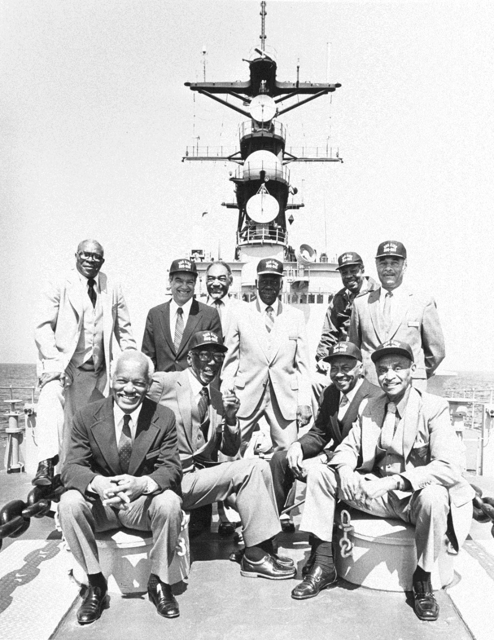 "The ""Golden Thirteen"" on board Kidd on April 1982. They are (seated, left to right): Jesse W. Arbor; Dalton L. Baugh; William S. White; Samuel E. Barnes; (standing, left to right): George C. Cooper; James E. Hare; John W. Reagan; Graham E. Martin; Wesley A. Brown; Frank E. Sublett.  Brown was the first African-American graduate of the U.S. Naval Academy. (NHHC Archives, NH 95625)"