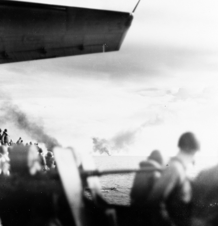 Sailors on board Kitkun Bay watch in horror as Gambier Bay burns and falls behind, 25 October 1944. (U.S. Navy Photograph 80-G-287512, National Archives and Records Administration, Still Pictures Division, College Park, Md.)