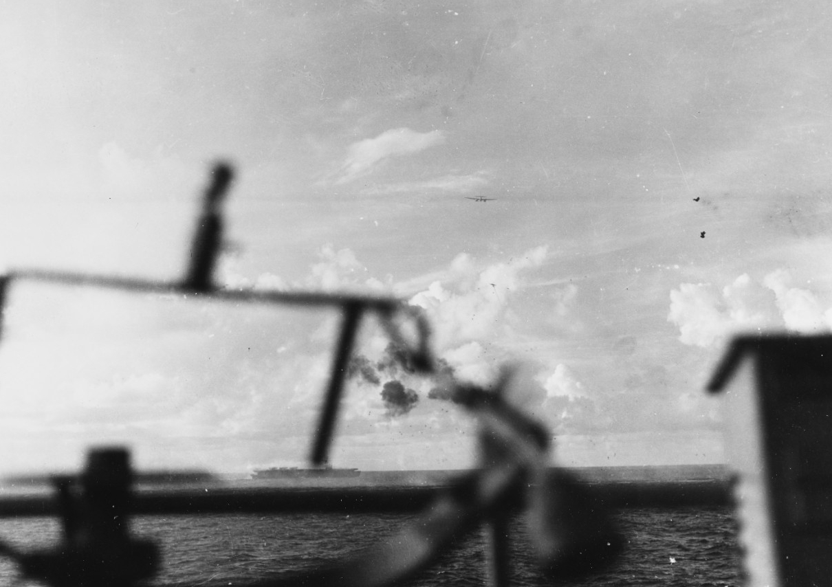Another enemy twin-engine planes passes over Gambier Bay during the fierce fighting off Saipan, 18 June 1944. Kitkun Bay fights off her attackers in the center of the picture, and another enemy plane is visible under the first one. (U.S. Navy Photograph 80-G-243430, National Archives and Records Administration, Still Pictures Division, College Park, Md.)