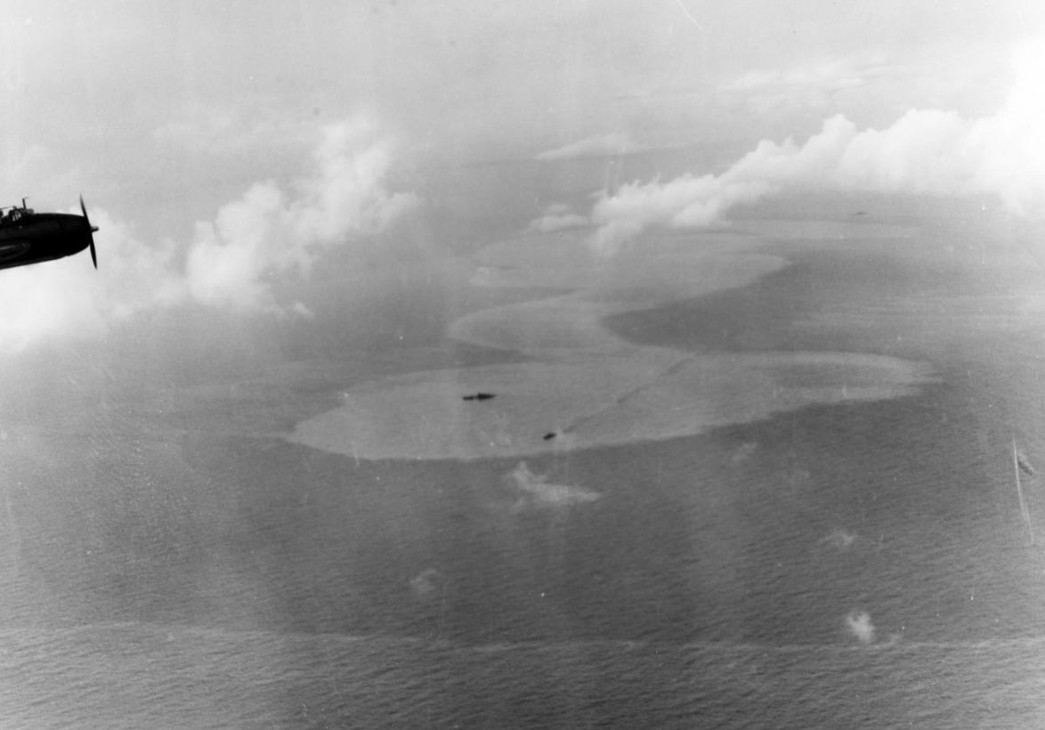 A Japanese heavy cruiser, possibly Chikuma, lies dead in the water, as a destroyer stands by to render assistance, 25 October 1944. An Avenger from one of the carriers, likely the wingman of the plane that takes the picture, flies in the upper left. A rapidly spreading oil slick is mute testimony to the damage inflicted on the cruiser. (U.S. Navy Photograph 80-G-287538, National Archives and Records Administration, Still Pictures Division, College Park, Md.)