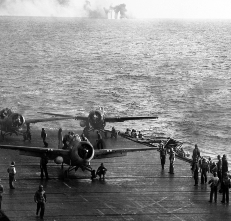 Men scramble to launch Wildcats as the enemy surprises Kitkun Bay off Samar, 25 October 1944. The fighter on the port quarter of the ship's flight deck turns quickly to get into the action as the planes launch rapidly in the desperate circumstances. Japanese shells splash around White Plains in the center distance. (U.S. Navy Photograph 80-G-287497, National Archives and Records Administration, Still Pictures Division, College Park, Md.)