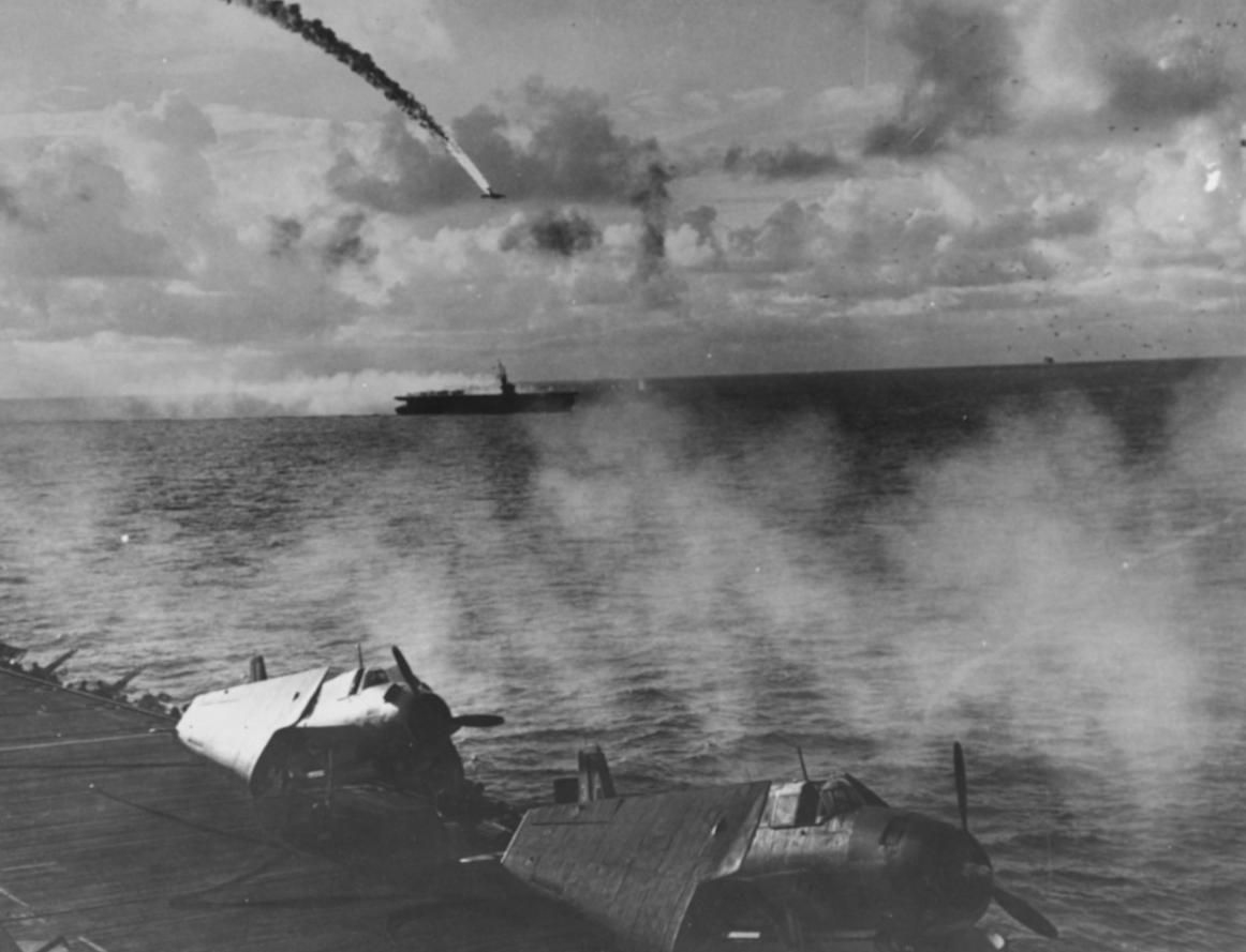 A Japanese twin-engine bomber crashes in flames as it attacks the escort carriers, 18 June 1944. Photographed from Kitkun Bay, with two of her Avengers, wings folded, parked on the flight deck, and guns blaze against the assailing enemy aircraft. (U.S. Navy Photograph 80-G-238363, National Archives and Records Administration, Still Pictures Division, College Park, Md.)