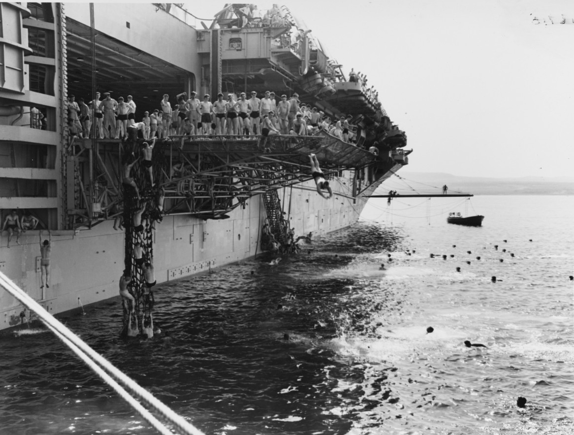 Swim call! Leyte sailors use her deck edge elevator as a diving platform, at Augusta Bay, Sicily, 27 May 1950. (U.S. Navy Photograph 80-G-415936, National Archives and Records Administration, Still Pictures Division, College Park, Md.)