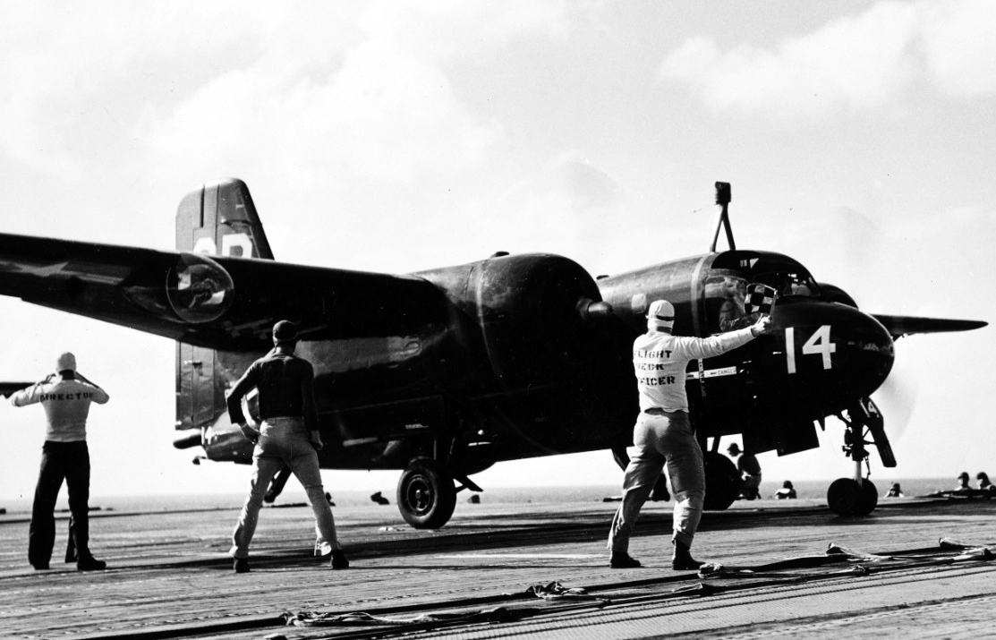 Grumman S2F-1 Tracker antisubmarine aircraft gets a 'go' signal from the Leyte flight deck officer as she is launched for antisubmarine patrol during LANTPHIBEX. The specially-designed aircraft were kept flying around the clock during the overseas transit of the amphibious force, and combined with sonar-equipped helicopters and blimps, provided effective protection against four 'enemy' subs. Quoted from the original caption, which was released by Leyte under a date of 1 November 1955. (Naval History and Heritage Command Photograph NH 97297)