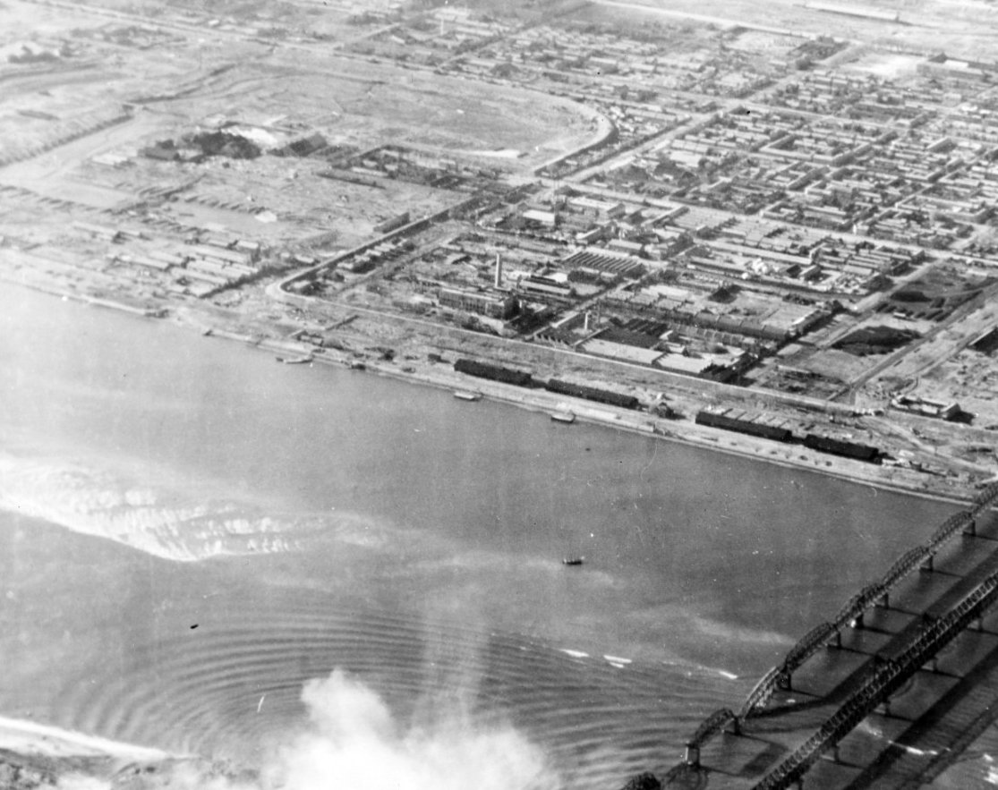 Bridges at Sinuiju, North Korea, under attack by planes from Leyte. The built-up area in the background is the Manchurian city of Antung. Bomb explosions in the lower part of the photo are on the Korean side of the Yalu River. Photograph is dated 22 November 1950, but may have been taken on 14 November. (U.S. Navy Photograph 80-G-423492, National Archives and Records Administration Still Pictures Division, College Park, Md.)