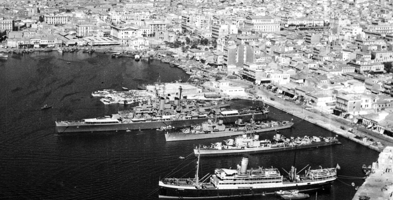 Little Rock lies at the Piraeus, the seaport for Athens, 6 September 1946, Mediterranean-moored (i.e., stern to shore) along with New (DD-818), Cone (DD-866), and Corry (DD-817). Note differing paint schemes on the two destroyers moored in the foreground, reflecting the transition from wartime to peacetime colors. (U.S. Navy Photograph 80-G-703058, National Archives and Records Administration, Still Pictures Division, College Park, Md.)