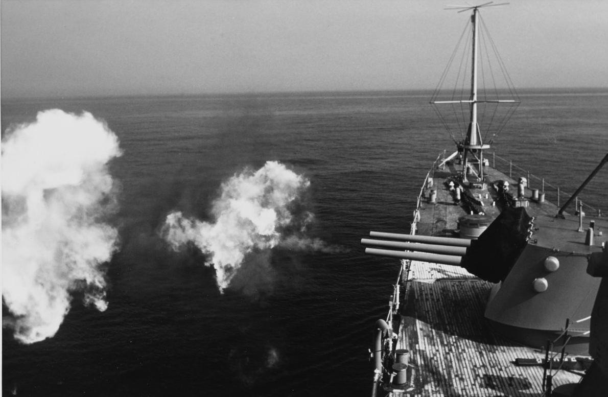 Little Rock firing her 6-inch/47 caliber guns during exercises on the Salto DiGuirra missile range off Sardinia, 23 April 1975. (Naval History and Heritage Command Photograph K-108728)