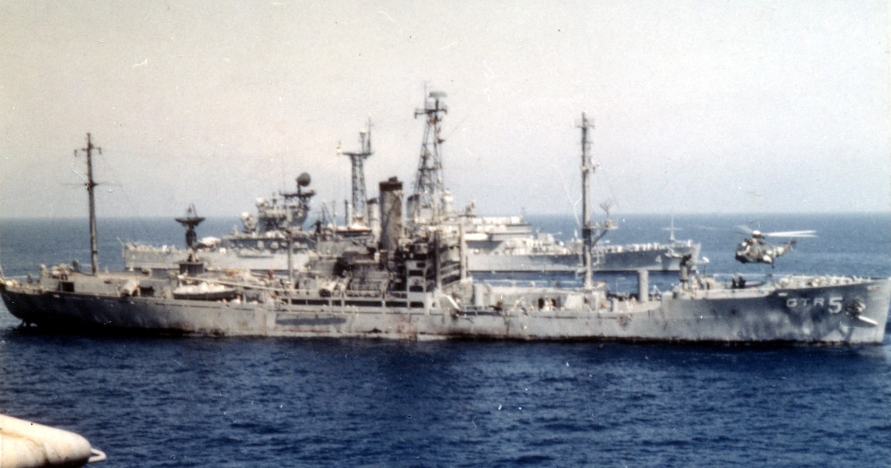 Liberty, her appearance reflecting the ferocity of the attack by Israeli planes and motor torpedo boats the previous afternoon, lists to starboard while Little Rock passes in the background and a helicopter lifts off  to transfer wounded to America (from which the photograph was taken), 9 June 1967. (U.S. Navy Photograph K-38435 (PH1 J. J. Kelly), National Archives and Records Administration, Still Pictures Division, College Park, Md.)