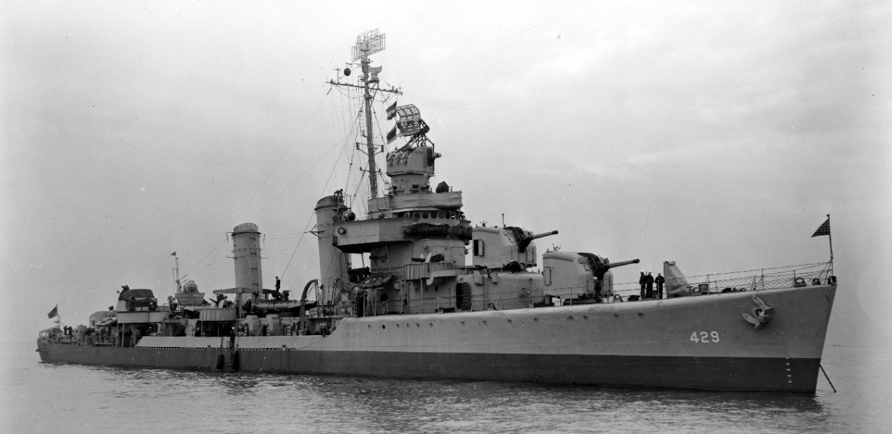 Livermore anchored at New York, 24 September 1943, showing her two-tone graded camouflage, the dividing line between upper and lower colors following the horizon instead of the sheer of the main deck. Close examination of the original print shows a sentry with a slung rifle just below 5-incher of Mt. 51 with two of his shipmates. Fenders are hung over the side of the ship near the ladder amidships. Note floater net baskets at bridge level. (U.S. Navy Bureau of Ships Photograph BS-53744, National Archives and Records Administration, Still Pictures Division, College Park, Md.)