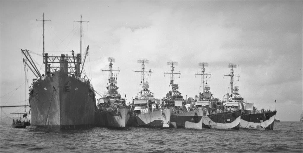 Longshaw (third ship from left) nested at Ulithi alongside the destroyer tender Markab (AD-21), between 2 and 10 December 1944; order of ships (L-R): Markab, Thatcher (DD-514), Longshaw, Preston (DD-795), Porterfield (DD-682), and Cassin Young (DD-793). Note that Thatcher has the early rounded bridge in the class's original design; that two of the ships have erected movie screens forward, and there is a gig moored at Cassin Young's bow. Also note the differences in the disruptive camouflage patterns from ship to ship, and the two sailors engaged in painting part of Longshaw's hull near her bow. (U.S. Navy Photograph by Lt. Cmdr. Charles Jacobs, 80-G-408161, National Archives and Records Administration, Still Pictures Division, College Park, Md,)
