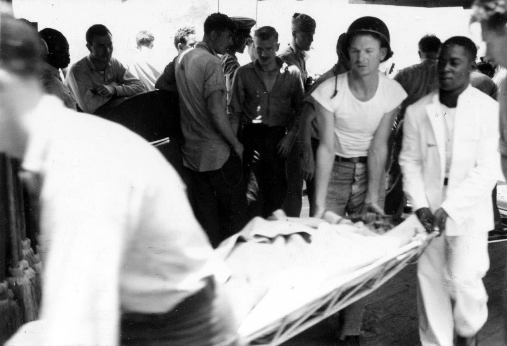 Salt Lake City (CA-25) sailors turn-to to carry a wounded Longshaw bluejacket to receive medical treatment, 18 May 1945. (U.S. Navy Photograph 80-G-343594, National Archives and Records Administration, Still Pictures Division, College Park, Md.)