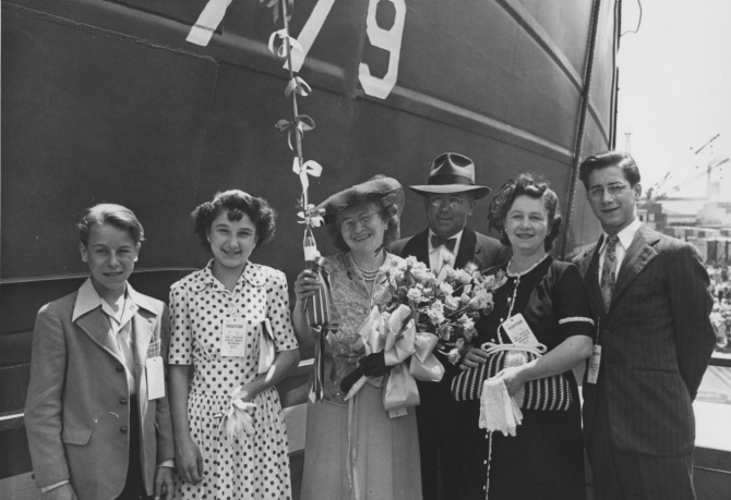 Mrs. Andrew Vavrek, LST-779's sponsor (center) holding the traditional bottle and bouquet, beams for the camera with others of the launching party before christening the ship that looms behind her, 1 July 1944. (U.S. Navy Bureau of Ships Photograph 19-N-67841, National Archives and Records Administration, Still Pictures Branch, College Park, Md.)