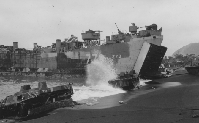 As waves crash against beached LVTs (the one in the foreground, 5A-30, named FELICE), LST-779 unloads at Iwo Jima, 26 February 1945. Suribachi looms in the background (R). Note weathered camouflage and duplicate identification numbers.  (U.S. Navy Photograph 80-G-317961, National Archives and Records Administration, Still Pictures Branch, College Park, Md.)