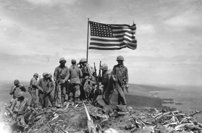 Risking sniper fire, marines gather around LST-779's colors as they snap in the wind at the summit of Suribachi, 23 February 1945, as photographed by Pvt. Bob Campbell, USMC. (U.S. Marine Corps Photograph RG-127-GW-319-112721, National Archives and Records Administration, Still Pictures Branch, College Park, Md.)