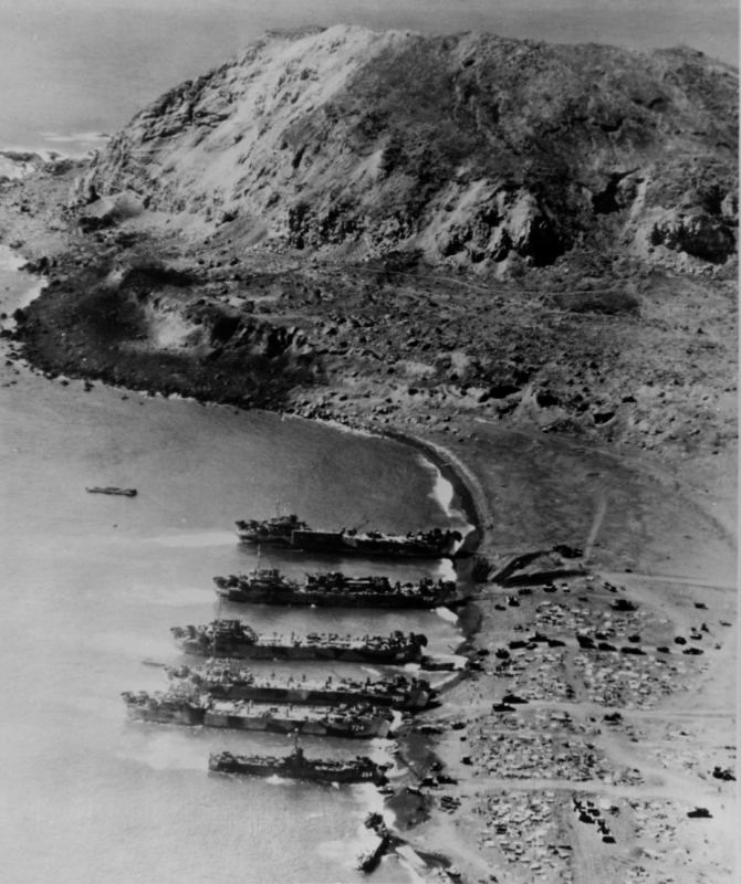 """... And the unloading of general cargo is proceeding"". Five tank landing ships and one medium landing ship nose into the dark sands of Iwo Jima on 24 February 1945. The view shows Beach Green 1, with Mount Suribachi in the background. The small wrecked ship in the foreground is Japanese. The landing ships include (from bottom to center): LSM-264, LST-724, LST-760, LST-788, LST-808 (with a LCT embarked), and LST-779 (carrying a pontoon causeway). (U.S. Navy Photograph NH 65314, Naval History and Heritage Command)"