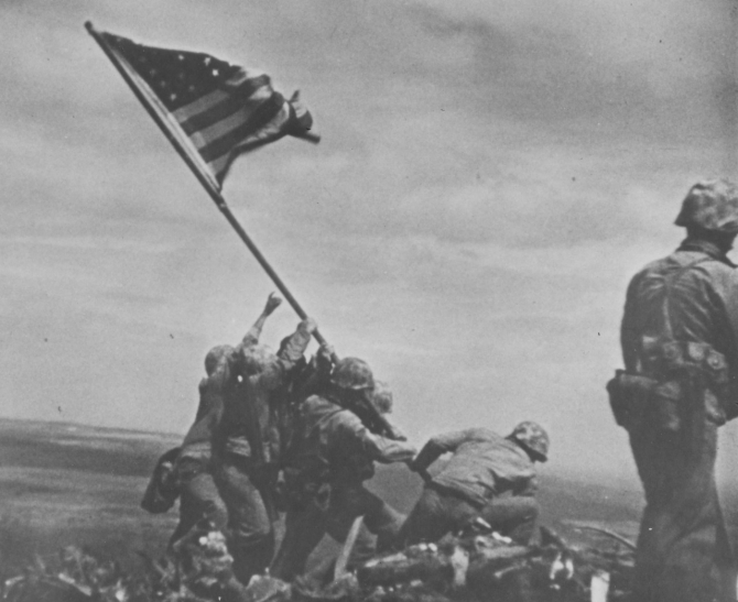 Marines raise the colors obtained from LST-779 on the summit of Mount Suribachi in this image captured on 16 millimeter motion picture film by SSgt. William H. Genaust, USMC, on 23 February 1945. (U.S. Marine Corps Photograph RG-127-GW-319-113057, National Archives and Records Administration, Still Pictures Branch, College Park, Md.)