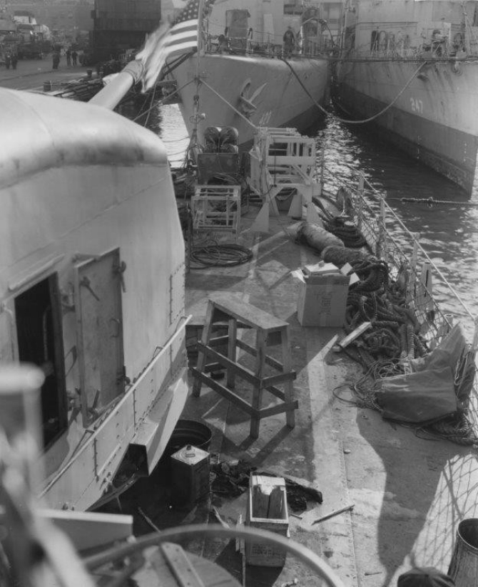 Looking aft from the port side past Madison's Mt. 55 (left) showing the typical clutter of a yard overhaul, New York Navy Yard, 1 January 1944. Upside-down cardboard National Biscuit Company box (to right of center of photo) appears to have the ship's identification number [425] marked on it. Charles F. Hughes (DD-428) and Goff (DD-247) lie moored astern, seen beyond the empty depth charge track and CS [chemical smoke] apparatus on the fantail. (U.S. Navy Bureau of Ships Photograph BS 59090, National Archives and Records Administration, Still Pictures Branch, College Park, Md.)