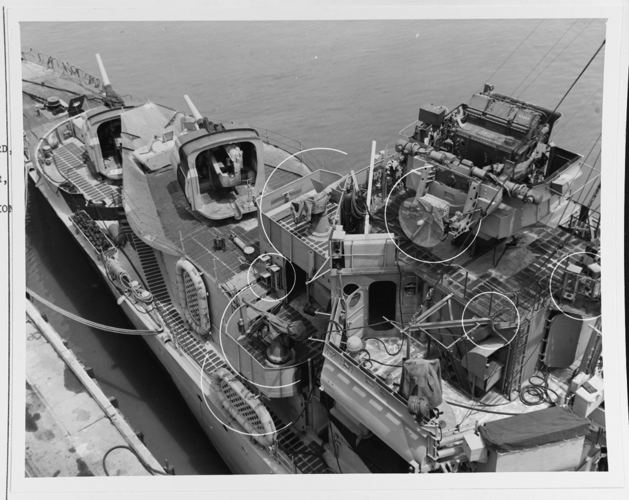 Close-up view of Mahan's forward superstructure, taken at Mare Island on 24 June 1944. View looks down on the port side of the pilothouse, and shows the destroyer's Mk. 33 gun director, with fire control radar antenna, in the upper right. Also seen are her two forward 5-inch gun mounts, non-skid deck treads, and life rafts. Circles indicate recent alterations to the ship. (U.S. Navy Bureau of Ships Photograph 19-N-67752, National Archives and Records Administration, Still Pictures Division, College Park, Md.)