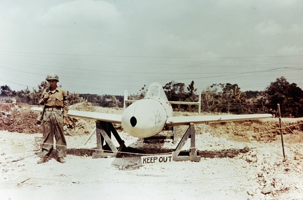 A captured Japanese Yokosuka MXY7 Ohka Model 11 suicide attack weapon guarded by an American MP at Yontan Airfield, Okinawa, circa April-May 1945. (U.S. Navy Photograph 80-G-K-4930, National Archives and Records Administration, Still Pictures Division, College Park, Md.).