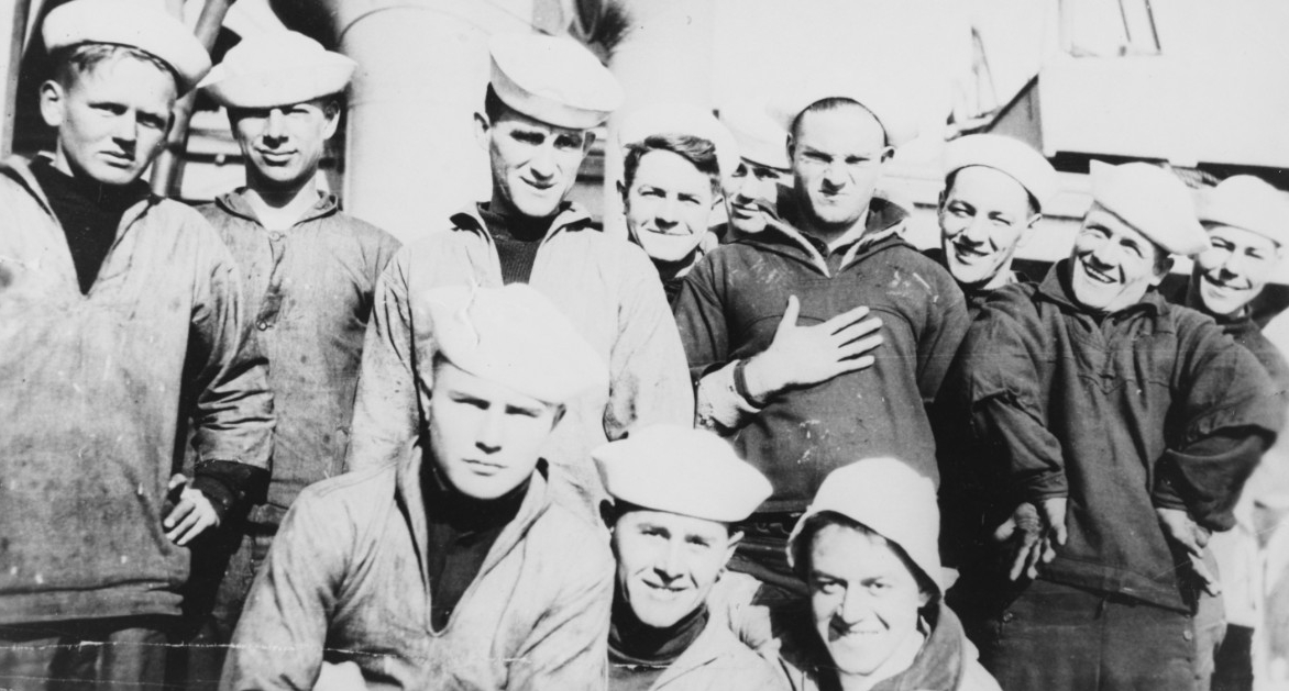 A group of sailors of the ship's company pose for the photographer's glass, 1917. One of the men, SN Hubert C. Rickert, stands defiantly with his hand on his chest. (Naval History and Heritage Command Photograph NH 93090)