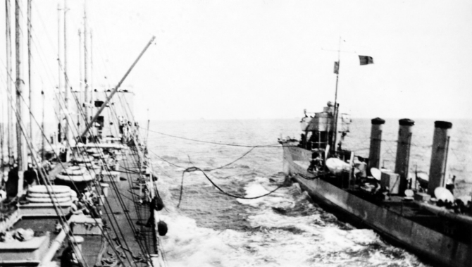 "Maumee replenishes McCall's fuel bunkers, 22 September 1917. Note red ""Baker"" refueling flag flying from the destroyer. (Naval History and Heritage Command Photograph NH 93098)."