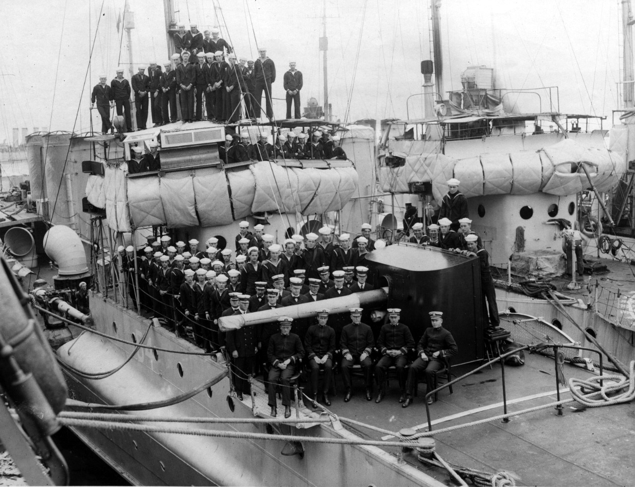 McDougal's ship's company arrayed for a group photograph, officers in the foreground, with chief petty officers immediately behind them. Note the shield on the forward gun and the framework to prevent the depression of the gun to fire into the forecastle, as well as the hinged pierced plate platforms to extend the working circle for the mount, the splinter mattresses hung on the forward part of the bridge (the only part of which that seems to be of solid construction is the chart desk on the starboard side), and the ship's identification number (54) painted on the hull beneath the bridge. (U.S. Navy Bureau of Ships Photograph, RG-19-E Collection, Box 7, Folder H, National Archives and Records Administration, Still Pictures Branch, College Park, Md.)