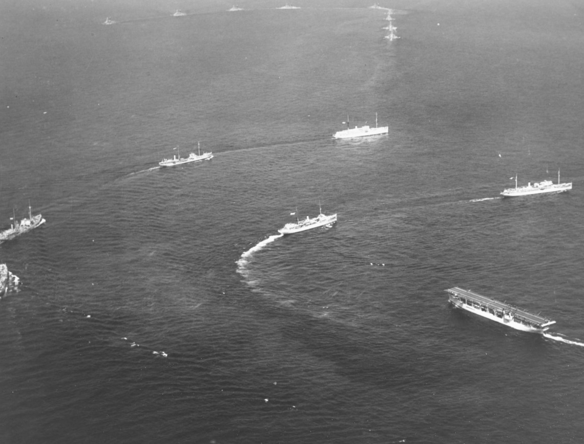 Ships of the Fleet Train maneuver during the fleet review off New York, 31 May 1934. Melville (right center) crosses the bow of Langley (CV-1), led by either Dobbin (AD-3) or Whitney (AD-4). Hospital ship Relief (AH-1) leads the next line, followed by a pair of oilers and another auxiliary. Nine battleships make a column turn to port, in the distance. (Naval History and Heritage Command Photograph NH 95716)