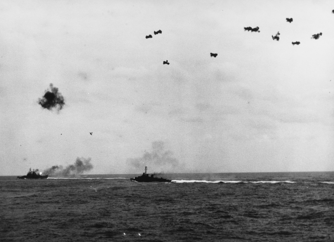 The ferocity of the defense against an attack by a kamikaze is seen here as viewed from Miami (her tracers can be seen at center) as a Mitsubishi A6M5 Zeke plunges through antiaircraft fire in an attempt to crash sister ship Vincennes off Okinawa, 6 April 1945, while a destroyer, bone-in-teeth, adds to the barrage. (U.S. Navy Photograph 80-G-324534, National Archives and Records Administration, Still Pictures Division, College Park, Md.)