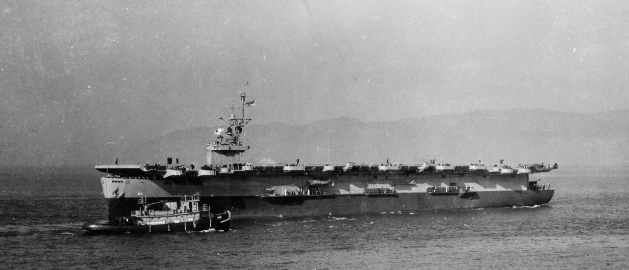 Midway, wearing the two-color camouflage originally applied to her, the dividing line running parallel to the horizon and not to the sheer of the main deck, backs down off Astoria as seen from sister ship Tripoli (CVE-64), 13 November 1943. Harbor tug Orono (YT-190) is passing close to the new escort carrier. (U.S. Navy Photograph 80-G-364706, National Archives and Records Administration, Still Pictures Division, College Park, Md.)