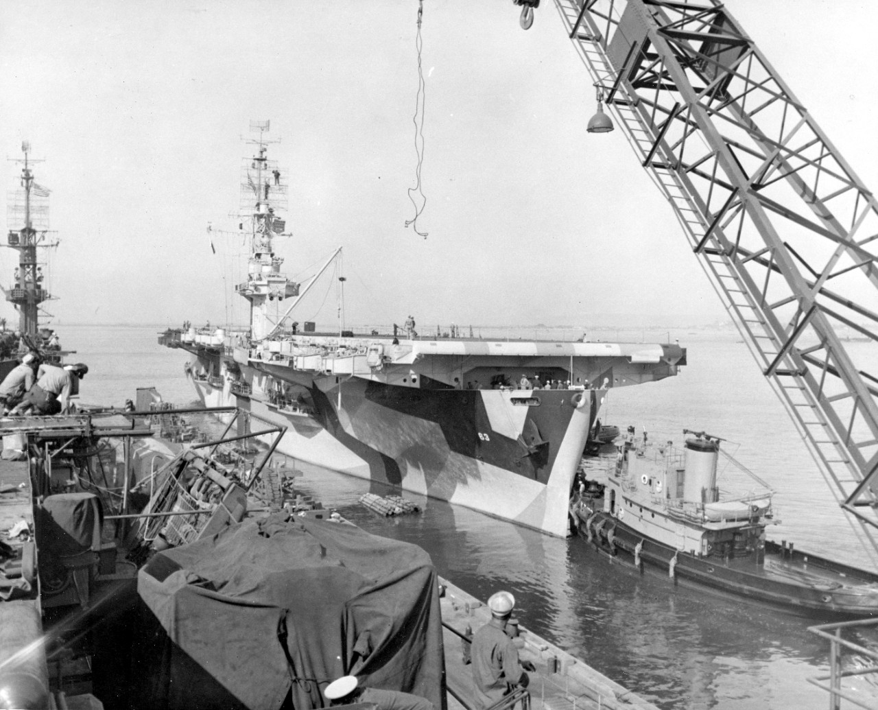 Midway, painted in a three-color disruptive camouflage, backs out of her berth at the Naval Repair Base, San Diego, following an availability there, assisted by harbor tugs, as seen from her sister ship White Plains (CVE-66), 10 April 1944. (U.S. Navy Photograph 80-G-384078, National Archives and Records Administration, Still Pictures Division, College Park, Md.)