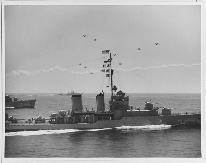 Patrol planes of VPs 7F, 9F, and 11F, operating from seaplane tender Wright (AV-1), fly a massed formation over Monaghan (foreground) and Dale, 14 September 1936. Monaghan's bow cuts deeply into the water as she makes speed while maneuvering. (Naval History and Heritage Command Photograph NH 67281)