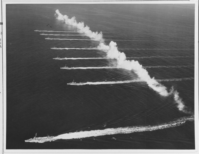 Ships of Destroyer Squadron (DesRon) 20 steam through a smokescreen laid by Consolidated P2Y-3s and Martin PM-1s of Patrol Squadrons (VPs) 7F, 9F, and 11F, during an exhibition staged for Movietone News off San Diego, Calif., 14 September 1936. The ships, from bottom to top are: Farragut (DD-348); Dewey (DD-349); Hull (DD-350); Macdonough (DD-351); Worden (DD-352); Dale (DD-353); Monaghan (DD-354) and Aylwin (DD-355). (Courtesy Cmdr. Robert L. Ghormley Jr., 1969, Naval History and Heritage Command Photograph NH 67293)