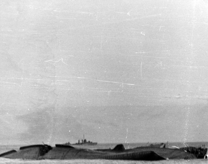 Yorktown sinks, as seen from an accompanying destroyer, just after dawn, 7 June 1942. Monaghan is in the left center distance. The carrier capsizes to port, exposing the turn of her starboard bilge. This view looks toward the ship's bottom from off her bow, with Yorktown's forefoot in the right foreground and her starboard forward 5-inch gun gallery beyond. The large hole made by one or two submarine torpedoes, severing the ship's forward bilge keel, is toward the left. (Naval History and Heritage Command Photograph NH 106003)