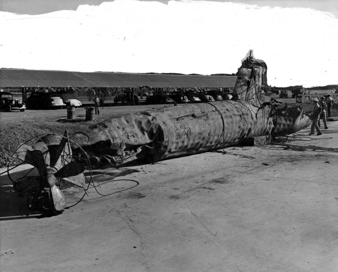 The Navy raises I-22tou's battered hulk at Pearl Harbor. The submarine's hull shows the effects of Monaghan's depth charges and ramming. A hole visible in the after part of the conning tower may be from a 5-inch shell. The upper background has been overpainted for censorship purposes. (Naval History and Heritage Command Photograph NH 54302)