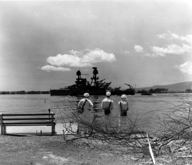 Nevada departing Pearl Harbor after temporary repair of bomb and torpedo damage received during the Japanese air raid on 7 December 1941. Photograph is dated 19 April 1942, possibly taken as the ship was leaving for a trial run. Note sailors watching, each carrying a gas mask container. Photographed by Photographer's Mate 2nd Class H.S. Fawcett. (U.S. Navy Photograph 80-G-64768 National Archives and Records Administration, Still Pictures Division, College Park, Md.)