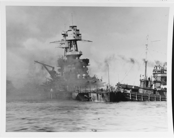 Nevada aground and burning off Waipio Point, after the end of the Japanese air raid. Ships assisting her, at right, are the harbor tug Hoga (YT-146) and the tender Avocet (AVP-4). (U.S. Navy Photograph 80-G-33020 National Archives and Records Administration, Still Pictures Division, College Park, Md.)