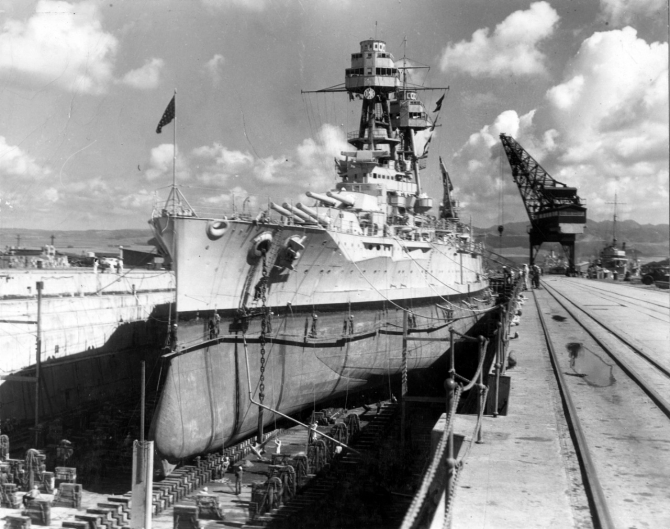 Nevada in Dry Dock No. 1 at the Pearl Harbor Navy Yard. Note the men painting her boot topping from stages rigged over the side, and the outline of her anti-torpedo blister where it merges with her forward hull. (Naval History and Heritage Command Photograph NH 50102)